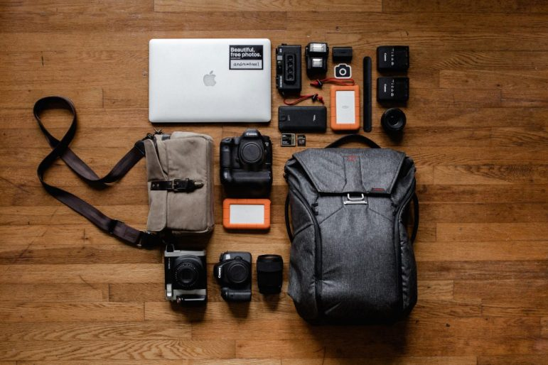 An assortment of items for an explorer's kit including a green canvas bag.